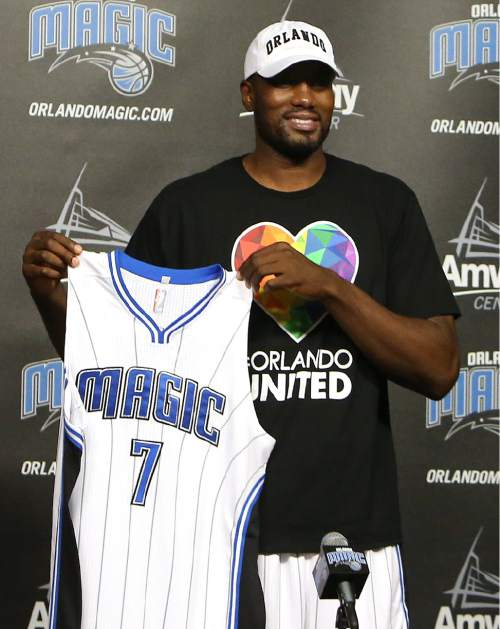 The Orlando Magic's Serge Ibaka holds up a jersey during a news conference Thursday, June 30, 2016, in Orlando, Fla. The Magic landed the veteran Ibaka in a trade with Oklahoma City that sent Victor Oladipo, Ersan Ilaysova and the rights to Domantas Sabonis, who was taken 11th overall in the draft. (Charles King/Orlando Sentinel via AP)