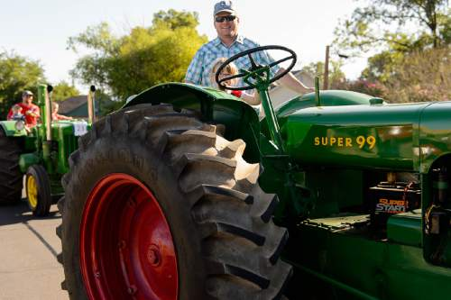 Trent Nelson  |  The Salt Lake Tribune 4-year-old Brielle Clyde drives a 1953 tractor, with help from Mark Clyde, in the Freedom Parade in Hurricane, Monday July 4, 2016.