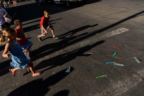 Trent Nelson  |  The Salt Lake Tribune Kids run for frozen treats during the Freedom Parade in Hurricane, Monday July 4, 2016.