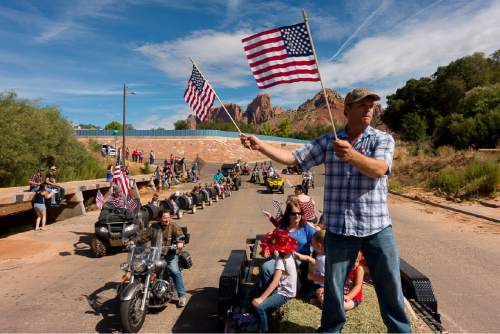 "Trent Nelson  |  The Salt Lake Tribune Patrick Pipkin waves flags and shouts, ""Freedom!"" as the Colorado City and Hildale Fourth of July Parade makes its way down Central Street in Hildale, UT, and Colorado City, AZ, as part of an Independence Day celebration Saturday July 2, 2016."