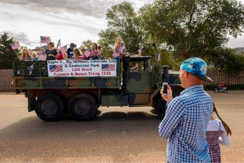 Trent Nelson  |  The Salt Lake Tribune Members of a local LDS ward wave flags as the Colorado City and Hildale Fourth of July Parade makes its way down Central Street in Hildale, UT, and Colorado City, AZ, as part of an Independence Day celebration Saturday July 2, 2016.