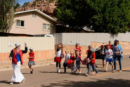 Trent Nelson  |  The Salt Lake Tribune A group of dancers pass a wall-off residence throwing candy and wave as the Colorado City and Hildale Fourth of July Parade makes its way down Central Street in Hildale, UT, and Colorado City, AZ, Saturday July 2, 2016.