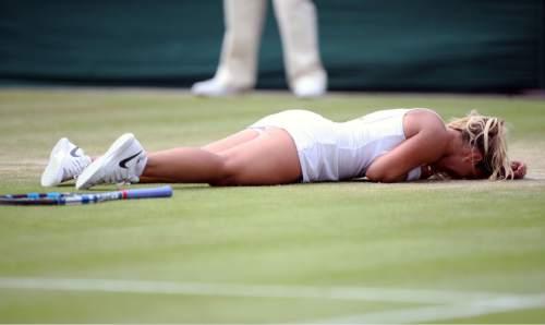 Dominika Cibulkova of Slovakia celebrates after beating Agnieszka Radwanska of Poland during their women's singles match on day eight of the Wimbledon Tennis Championships in London, Monday, July 4, 2016. (Anthony Devlin PA via AP)