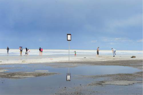 Scott Sommerdorf   |  The Salt Lake Tribune   Tourists enjoy walking on the flooded salt flats beyond one of the numerous signs warning motorists to stay off the salt flats near the Bonneville Speedway, Friday, May 27, 2016.