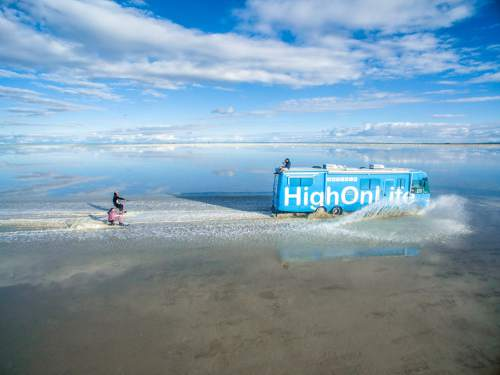 This screenshot of the High On Life Facebook page shows Parker Heuser and Alexey Lyakh waterskiing behind an RV on the Salt Flats west of Salt Lake City.