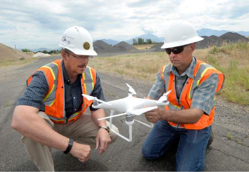Al Hartmann  |  The Salt Lake Tribune  Reid Demman, Salt Lake County Surveyor, left, and Mark Miller, certified pilot in charge ready a helicopter drone to fly over the old Welby gravel pit in West Jordan Thurs. June 30.  The drone will fly over the 160 acre area and take photos and plot coordinates in just a few minutes. The old gravel pit is to be made into a park.  The Salt Lake County Surveyor's Office is one of the few public agencies nationwide to receive FAA approval to operate a drone for any number of  projects for it and other government agencies.