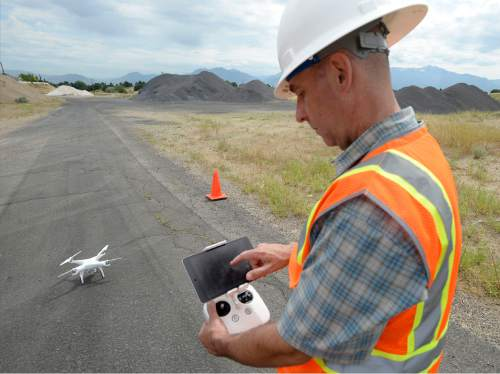 Al Hartmann  |  The Salt Lake Tribune  Mark Miller, certified pilot in charge with the Salt Lake County Surveyor office , programs a helicopter drone to fly over the old Welby gravel pit in West Jordan Thurs. June 30.  The drone will fly over the 160 acre area and take photos and plot coordinates in just a few minutes. The old gravel pit is to be made into a park.  The Salt Lake County Surveyor's Office is one of the few public agencies nationwide to receive FAA approval to operate a drone for any number of  projects for it and other government agencies.