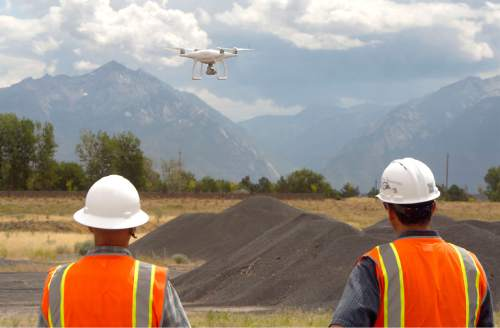 Al Hartmann  |  The Salt Lake Tribune  Mark Miller, certified pilot in charge, left, and Reid Demman, Salt Lake County Surveyor, watch as helicopter drone starts it fly over the old Welby gravel pit in West Jordan Thurs. June 30.  The drone will fly over the 160 acre area and take photos and plot coordinates in just a few minutes. The old gravel pit is to be made into a park.  The Salt Lake County Surveyor's Office is one of the few public agencies nationwide to receive FAA approval to operate a drone for any number of  projects for it and other government agencies.