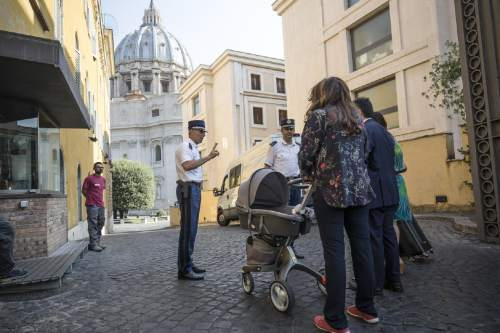 Public relations expert Francesca Chaouqui, right, back to camera, arrives with her newly born son Pietro, at the Vatican for her trial, Tuesday, July 5, 2016.  Two Italian journalists who wrote books detailing Vatican mismanagement face trial in a Vatican courtroom along with three people accused of leaking them the information in a case that has drawn scorn from media watchdogs. (Giuseppe Lami/ANSA via AP Photo)