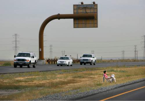 Scott Sommerdorf  |  Salt Lake Tribune   Carolyln Thomas waited by the northbound side of the Legacy Parkway just before the UHP also closed the southbound side prior to the Hess Cancer Run. She set up her chair to watch her husband Kent run the race. UHP closed Legacy Parkway for the Hess Cancer Foundation's half marathon fundraiser Saturday, August 29, 2009.