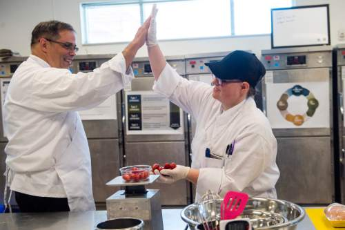 Chris Detrick  |  The Salt Lake Tribune Army veteran Cliff Hutson, and Navy veteran Jessica Beck,  high five during the second day of Culinary Command, a training program for veterans and active military. Wednesday June 1, 2016.