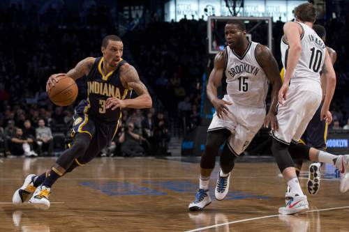 Indiana Pacers guard George Hill (3) drives to the basket against Brooklyn Nets guard Donald Sloan (15) and guard Sergey Karasev (10) during the first half of an NBA basketball game, Saturday, March 26, 2016, at  New York. The Nets won 120-110.  (AP Photo/Mary Altaffer)