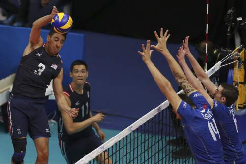 U.S. player Taylor Sander, left, spikes the ball against France's defense during a Volleyball World League match at the Maracanazinho gymnasium in Rio de Janeiro, Brazil, Friday, July 17, 2015. (AP Photo/Leo Correa)