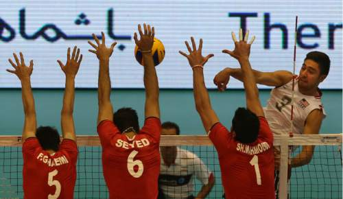 USA volleyball player Taylor Sander, right, smashes the ball against Iran's Farhad Ghaemi, left, Mohammad Mousavi Eraghi, second left, and Shahram Mahmoudi during Men's Volleyball World League, at the Azadi (Freedom) stadium in Tehran, Iran, Friday, June 19, 2015. Iran defeated the United States 3-0. (AP Photo/Vahid Salemi)