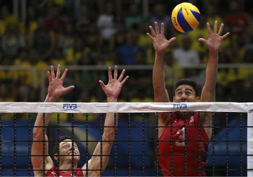 U.S. Taylor Sander, right, and David Lee, work to block the ball during a Volleyball World League match against Brazil, at the Maracanazinho gymnasium in Rio de Janeiro, Brazil, Thursday, July 16, 2015. Brazil won 3-1. (AP Photo/Leo Correa)