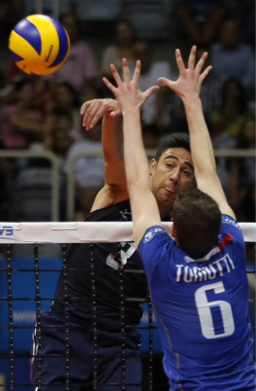 U.S. player Taylor Sander spikes the ball against France's Benjamin Toniutti during a Volleyball World League match at the Maracanazinho gymnasium in Rio de Janeiro, Brazil, Friday, July 17, 2015. (AP Photo/Leo Correa)