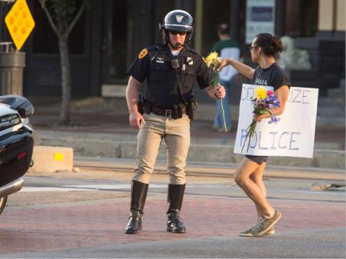 Rick Egan  |  The Salt Lake Tribune  Jared Urbina hands flowers to a Salt Lake City Policeman as he stops traffic for the marchers, during an emergency protest against police brutality to support the protests in Baton Rouge and St. Paul, Saturday, July 9, 2016.