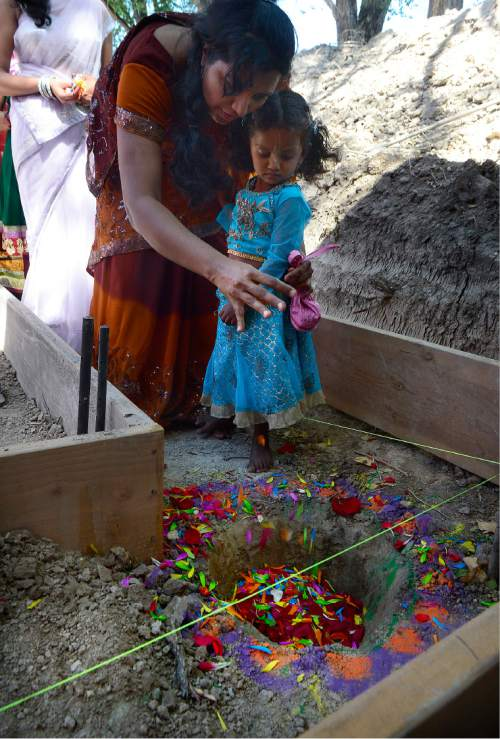 Scott Sommerdorf   |  The Salt Lake Tribune   Padma Priya and her daughter offer flower petals and five elements to Lord Anantshesha buried in the foundation as protection for the new Krishna Temple designed by Vaibhavi Devi, who worked on the Spanish Fork Krishna Temple, Sunday, July 10, 2016.
