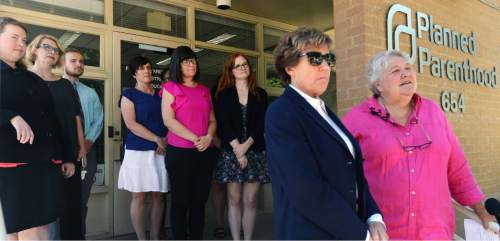 """Steve Griffin / The Salt Lake Tribune  Karrie Galloway, CEO and President of Planned Parenthood Association of Utah, is joined by attorney Peggy Tomsic and others as they talk to the media outside the Planned Parenthood office in Salt Lake City Tuesday July 12, 2016.  Utah Gov. Gary Herbert's order to strip $272,000 in federal funding from Planned Parenthood Association of Utah was likely made to """"punish"""" the organization, a federal appeals court ruled Tuesday. In a split 2-1 decision, the 10th Circuit Court of Appeals granted a preliminary injunction to Planned Parenthood, reversing a lower court decision and restoring the flow of federal funds to the reproductive health organization."""
