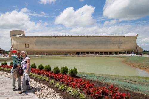 Visitors take a selfie as a replica Noah's Ark stands in the distance at the Ark Encounter theme park during a media preview day, Tuesday, July 5, 2016, in Williamstown, Ky. The long-awaited theme park based on the story of a man who got a warning from God about a worldwide flood will debut in central Kentucky this Thursday. The Christian group behind the 510 foot-long wooden ark says it will demonstrate that the stories of the Bible are true. Its construction has rankled opponents who say the attraction will be detrimental to science education. (AP Photo/John Minchillo)