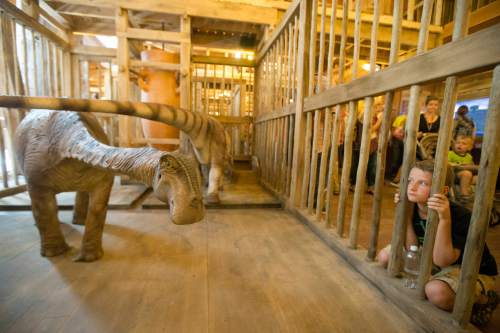 A visitor looks into a cage containing a model dinosaur inside a replica Noah's Ark at the Ark Encounter theme park during a media preview day, Tuesday, July 5, 2016, in Williamstown, Ky. The long-awaited theme park based on the story of a man who got a warning from God about a worldwide flood will debut in central Kentucky this Thursday. The Christian group behind the 510 foot-long wooden ark says it will demonstrate that the stories of the Bible are true. Its construction has rankled opponents who say the attraction will be detrimental to science education. (AP Photo/John Minchillo)