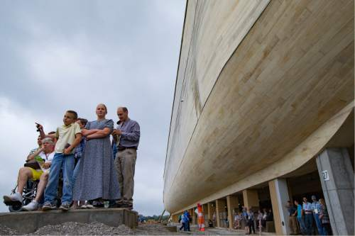 Visitors roam the Ark Encounter theme park as a replica of Noah's Ark stands in the background during a media preview day, Tuesday, July 5, 2016, in Williamstown, Ky. The long-awaited theme park based on the story of a man who got a warning from God about a worldwide flood will debut in central Kentucky this Thursday. The Christian group behind the 510 foot-long wooden ark says it will demonstrate that the stories of the Bible are true. Its construction has rankled opponents who say the attraction will be detrimental to science education. (AP Photo/John Minchillo)