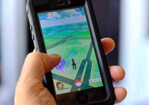 Pokemon Go is displayed on a cell phone in Los Angeles on Friday, July 8, 2016. Just days after being made available in the U.S., the mobile game Pokemon Go has jumped to become the top-grossing app in the App Store. And players have reported wiping out in a variety of ways as they wander the real world, eyes glued to their smartphone screens, in search of digital monsters. (AP Photo/Richard Vogel)