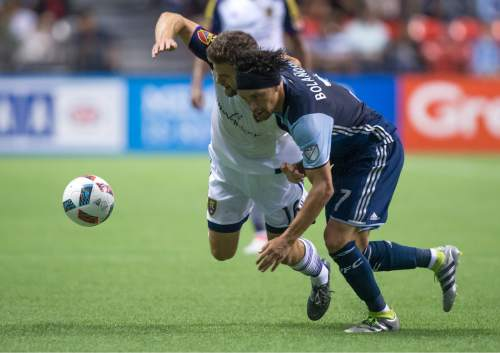 Real Salt Lake's Chris Wingert, back, and Vancouver Whitecaps' Christian Bolanos collide during the second half of an MLS soccer match on Wednesday July 13, 2016, in Vancouver, British Columbia. (Darryl Dyck/The Canadian Press via AP)