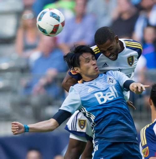 Vancouver Whitecaps' Masato Kudo, front, of Japan, and Real Salt Lake's Aaron Maund battle for the ball during the first half of an MLS soccer game on Wednesday July 13, 2016, in Vancouver, British Columbia. (Darryl Dyck/The Canadian Press via AP)