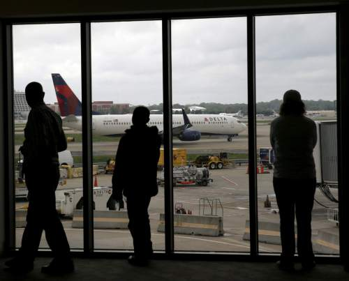 FILE - In this photo taken Tuesday, April 14, 2015, file photo, Delta Air Lines passengers watch as a Delta plane taxis at Hartsfield–Jackson Atlanta International Airport, in Atlanta. Most airlines have dropped bereavement fares; funerals are just one more last-minute trip. Among the largest U.S. airlines, only Delta Air Lines and Alaska Airlines still offer so-called bereavement fares. Those tickets, however, come with a big caveat. (AP Photo/Charles Rex Arbogast, File)