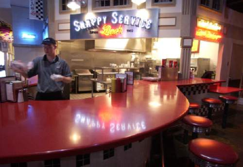 Trent Nelson     The Salt Lake Tribune  Josh Bowles serves up a hamburger with fries at Snappy Service August 27 2002. The restaurant is now located in the Jordan Commons, is marking its 100th anniversary.