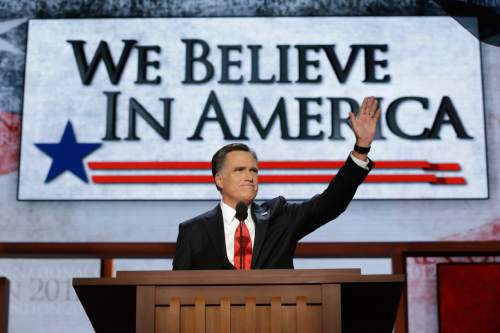 """FILE - In this Aug. 30, 2012, file photo Republican presidential nominee Mitt Romney addresses the Republican National Convention in Tampa, Fla. When Romney stood up to accept the Republican nomination for the presidency, the theme of the night was on the giant screen behind him: """"We Believe In America."""" The sentiment is on the side of his campaign plane, too. The suggestion is that the other party, led by President Barack Obama, does not believe in America, chiefly Obama.  (AP Photo/Charles Dharapak, File)"""