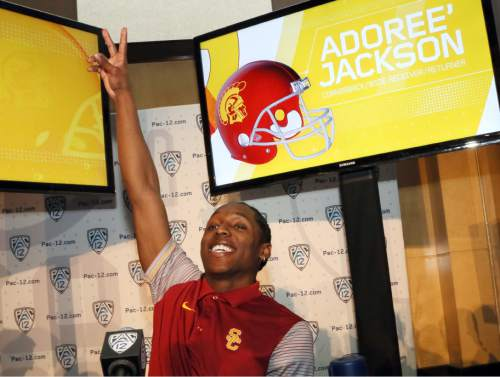 """Southern California's Adoree' Jackson flashes a 'V"""" sign as he sees coach Clay Helton at the Pac-12 NCAA college football media day in Los Angeles Thursday, July 14, 2016. Jackson is back from a seven-month break from football while he tried to qualify for the U.S. Olympic track team, and the multi-talented athlete plans to focus primarily on playing defense this fall. (AP Photo/Reed Saxon)"""