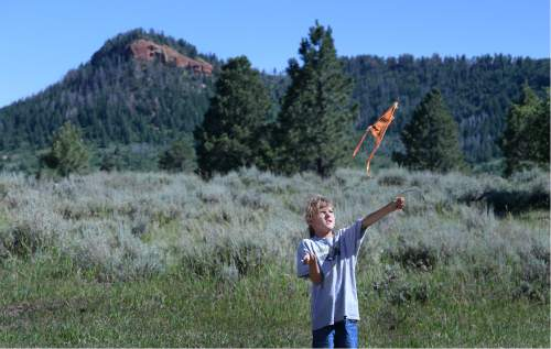 Scott Sommerdorf   |  The Salt Lake Tribune   Dineh native 9-year old Donald West Jr. plays with a kite with one of the Bears Ears in the background as a meeting with native people and U.S. Interior Secretary Sally Jewell proceeds in a meadow atop the Bears Ears, Friday, July 15, 2016.