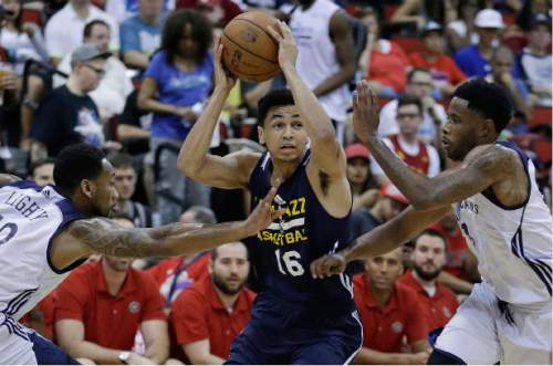 Utah Jazz's Marcus Paige, center, drives through New Orleans Pelicans' David Lighty Jr, left, and Larry Drew II, right, during the first half of an NBA summer league basketball game, Sunday, July 10, 2016, in Las Vegas. (AP Photo/John Locher)