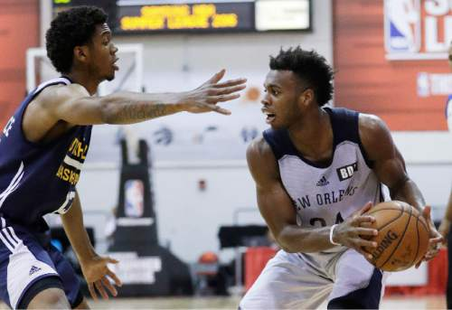 New Orleans Pelicans' Buddy Hield drives around Utah Jazz's Tyrone Wallace during the second half of an NBA summer league basketball game, Sunday, July 10, 2016, in Las Vegas. (AP Photo/John Locher)