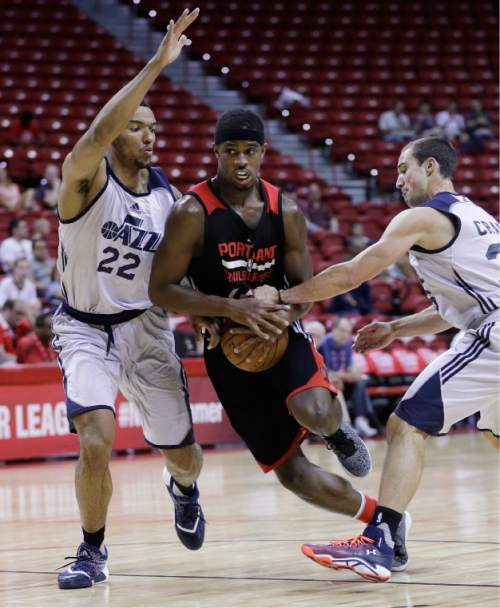 Portland Trail Blazers' CJ Fair, center, drives between Utah Jazz's Joel Bolomboy, left, and Aaron Craft during the first half of an NBA summer league basketball game Wednesday, July 13, 2016, in Las Vegas. (AP Photo/John Locher)