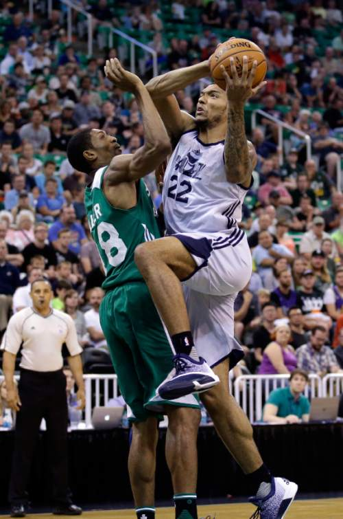 Utah Jazz's Joel Bolomboy (22) drives to the basket as Boston Celtics' Malcolm Miller defends during the second half of an NBA summer league basketball game Tuesday, July 5, 2016, in Salt Lake City. (AP Photo/Rick Bowmer)