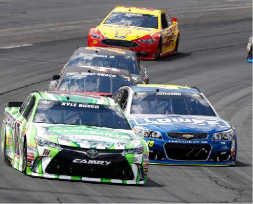 Kyle Busch (18) passes Jimmie Johnson (48) to take an early lead in the New Hampshire 301 auto race at New Hampshire Motor Speedway Sunday, July 17, 2016, in Loudon, N.H. (AP Photo/Jim Cole)