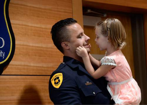 Al Hartmann  |  The Salt Lake Tribune  SLCPD Officer Ben Hone gets a pinch on the cheek by his daugher Adi, 4, before being presented the National Association of Chiefs of Police and the American Police Hall of Fame the Officer of the Year award Monday July 18 in Salt Lake City.