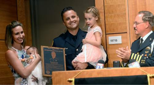 Al Hartmann  |  The Salt Lake Tribune  Chief Jack Rinchich of the National Association of Chiefs of Police and the American Police Hall of Fame, right,  presents SLCPD Officer Ben Hone with the Officer of the Year award Monday July 18 in Salt Lake City.  His wife Lauren and 11-week-old son, Oakley, left and daughter Adi, 4 join him in the ceremony.   Officer of the Year awards ceremony honors Officer Ben Hone, who last September shot and killed a man who had broken into an apartent shared by two sisters. When Hone arrived, Robert Richard Berger had stabbed Breann Lasley in the abdomen and was holding her from behind. As Berger pulled the knife out and his head was tipped breifly out from behnd the woman's, Hone saw his shot and took it. The shooting was later ruled justified.
