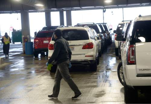 Al Hartmann  |  The Salt Lake Tribune  Workers push returned rental cars at Salt Lake International Airport's newly opened quick turn around facility Monday March 28.  The airport just just completed the car rental maintainence facility a couple months ago.  It is an early part of the $1.8 billion terminal redevelop program.