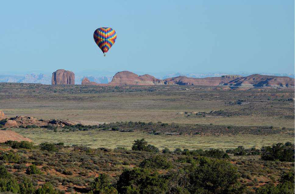 Scott Sommerdorf   |  The Salt Lake Tribune   A hot air ballon flies over the area on the way to Gemini Bridges near Moab as Interior Secretary Sally Jewell tours the area, Thursday, July 14, 2016.