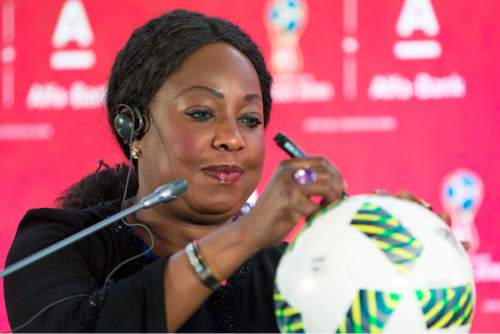 FIFA Secretary General Fatma Samoura signs an official FIFA tournament ball during a news conference in Moscow, Russia, Monday, July 18, 2016, during the FIFA sponsorship event with Russian Alfa Bank. FIFA has filled the first of 20 sponsor slots for the 2018 World Cup in a new program that stalled during its corruption crisis. FIFA says Russian bank Alfa-Bank has bought one of four European slots in a 'Regional Supporter' category. (AP Photo/Pavel Golovkin)