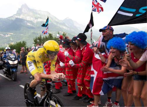 Supporters cheer Britain's Chris Froome, wearing the overall leader's yellow jersey as he rides during the eighteenth stage of the Tour de France cycling race, an individual time trial over 17 kilometers (10.6 miles) with start in Sallanches and finish in Megeve, France, Thursday, July 21, 2016. (AP Photo/Peter Dejong)