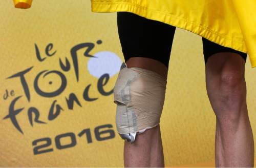 Britain's Chris Froome, his knee bandaged after his crash, puts on the overall leader's yellow jersey on the podium after the nineteenth stage of the Tour de France cycling race over 146 kilometers (90.7 miles) with start in Albertville and finish in Saint-Gervais Mont Blanc, France, Friday, July 22, 2016. (AP Photo/Christophe Ena)