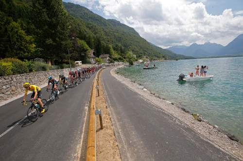 The pack with Britain's Chris Froome, wearing the overall leader's yellow jersey, rides along Annecy Lake during the nineteenth stage of the Tour de France cycling race over 146 kilometers (90.7 miles) with start in Albertville and finish in Saint-Gervais Mont Blanc, France, Friday, July 22, 2016. (AP Photo/Christophe Ena)
