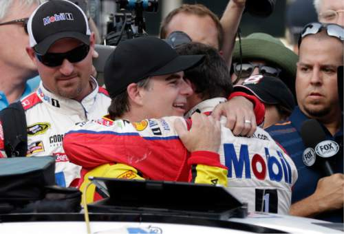 Jeff Gordon, center left, hugs Tony Stewart following the Brickyard 400 NASCAR Sprint Cup auto race at Indianapolis Motor Speedway in Indianapolis, Sunday, July 24, 2016. (AP Photo/Rob Baker)