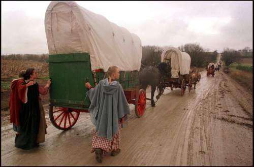 Rick Egan     Tribune file photo  Girls walk alongside their during a pioneer reenactment in 1997.