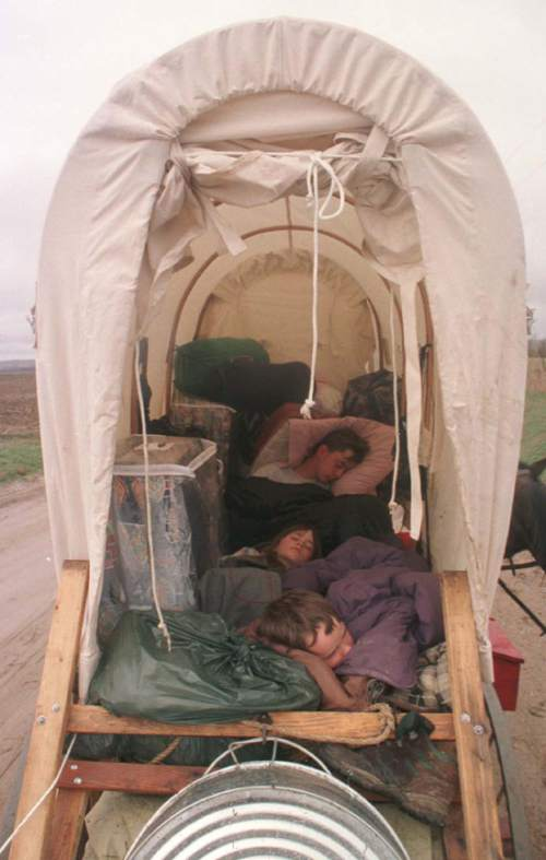 Rick Egan  |  Tribune file photo  Trek participants sleep in the back of a wagon during a 1997 wagon train reenactment in Wyoming.